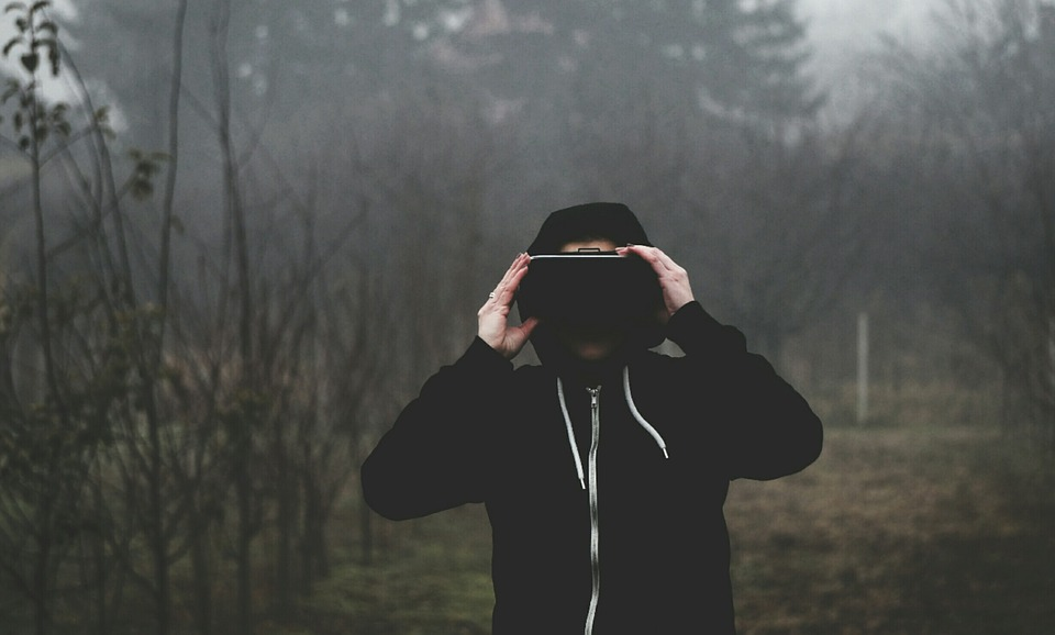 Photo d'un homme qui porte un casque VR dans la forêt